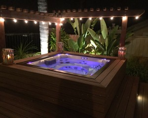 Outdoor hot tub illuminated by exterior lighting at night.
