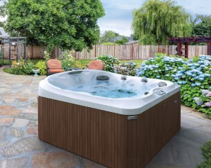 Jacuzzi Hot Tub installed in a backyard outside of a modern home.