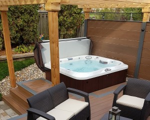 Jacuzzi Hot Tub installed in a backyard with steps, a privacy fence and furniture.